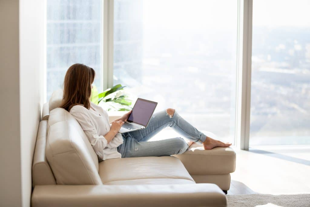 Woman with laptop in living room with amazing view
